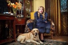Kvinna i en stol med en hund Royaltyfria Foton