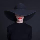 kvinna i en stor svart hatt Fotografering för Bildbyråer