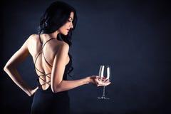 Kvinna i en svart klänning med ett exponeringsglas i hand arkivfoton