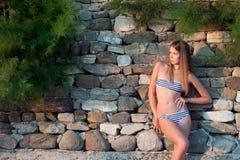 Kvinna i en swimwear på stenväggen Fotografering för Bildbyråer