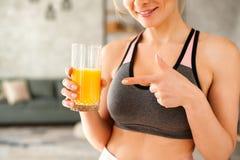Kvinna i en träningsoverall som dricker orange fruktsaft royaltyfri foto