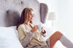 Kvinna i en tröja som dricker kaffe eller te royaltyfri bild