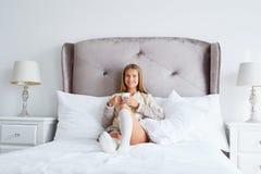 Kvinna i en tröja som dricker kaffe, medan ligga i säng royaltyfria foton