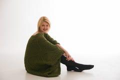 Kvinna i en tröja som ler på en vit bakgrund Fotografering för Bildbyråer