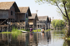 Kvinna i en uppstyltad by på sjön Arkivfoton