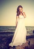 Kvinna i en vit klänning på stranden vid havet Fotografering för Bildbyråer
