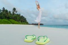 Kvinna i en vit klänningdans på den tropiska stranden mot closeupen för flipmisslyckanden Royaltyfri Foto