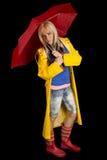 Kvinna i ett gult regnlag och ett rött paraply på svart se royaltyfria foton