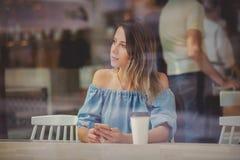 Kvinna i ett kafé och ett drickakaffe och bruksmobiltelefon, medan sitta vid fönstret arkivfoton
