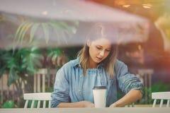 Kvinna i ett kafé och ett drickakaffe, medan sitta vid fönstret arkivbild