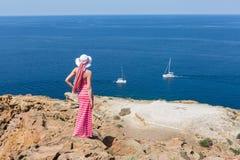 Kvinna i ett långt sommarklänninganseende på ett klippahav Fotografering för Bildbyråer
