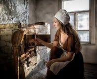 Kvinna i ett lantligt klänningsammanträde bredvid den gamla ugnen i ett förstört övergett hus arkivbilder