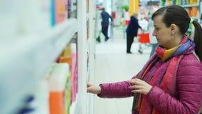 Kvinna i ett marknadslager som tänker vad för att köpa stock video