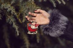 Kvinna i ett pälslag som dekorerar en julgran Royaltyfri Fotografi