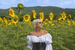 Kvinna i ett solrosfält arkivfoton