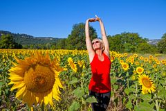 Kvinna i ett solrosfält royaltyfri fotografi