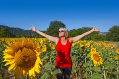 Kvinna i ett solrosfält royaltyfri bild