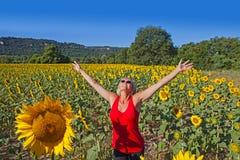 Kvinna i ett solrosfält arkivbild