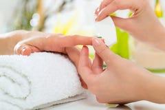Kvinnan spikar in salonghälerimanicuren Royaltyfri Fotografi
