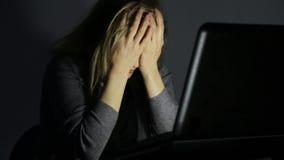 Kvinna i exponeringsglas genom att använda datoren i ett mörkt rum, blickar på bildskärmen och starter att få frustrerat