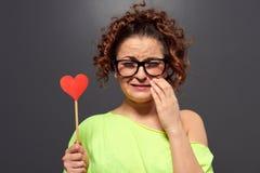 Kvinna i exponeringsglas med bruten hjärta Arkivbild