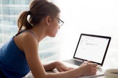 Kvinna i exponeringsglas som ser bärbar datorskärmen som tar anmärkningar royaltyfri foto