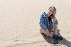 Kvinna i exponeringsglas som sitter i sanden arkivfoton