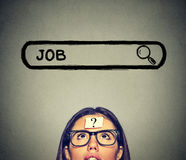 Kvinna i exponeringsglas som tänker söka efter ett nytt jobb som isoleras på grå väggbakgrund Arkivfoto