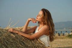 Kvinna i fält vid solnedgången royaltyfria bilder