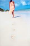 Kvinna i färgrik klänning som går på strandhavet som lämnar fotspår Arkivfoton