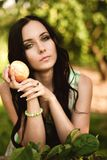 Kvinna i färgrik maxi klänning med asken med äpplen i en solig gar Royaltyfri Fotografi