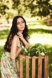 Kvinna i färgrik maxi klänning med asken med äpplen i en solig gar Royaltyfria Bilder