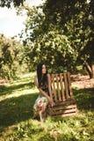 Kvinna i färgrik maxi klänning med asken med äpplen i en solig gar Arkivbild