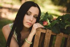 Kvinna i färgrik maxi klänning med asken med äpplen i en solig gar Royaltyfri Foto