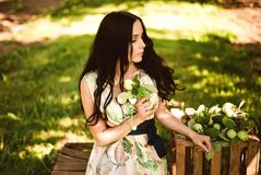 Kvinna i färgrik maxi klänning med asken med äpplen i en solig gar Royaltyfria Foton
