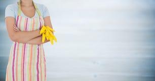 Kvinna i förkläde med armar vikta och handskar av mot oskarp grå wood panel Royaltyfri Bild