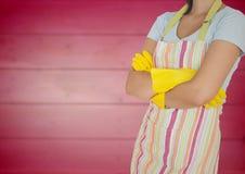 Kvinna i förkläde med armar vikta och handskar på mot oskarp rosa wood panel Arkivbilder