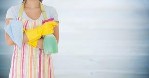 Kvinna i förkläde med gula handskar och rengöringsmedel mot oskarp grå wood panel Fotografering för Bildbyråer