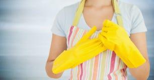 Kvinna i förkläde med gula handskar på mot oskarp grå wood panel Royaltyfri Bild