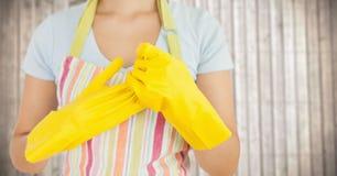 Kvinna i förkläde med handskar mot oskarp wood panel Royaltyfria Bilder