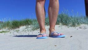 Kvinna i flipmisslyckanden på den sandiga stranden stock video