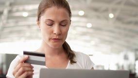 Kvinna i flygplats som direktanslutet shoppar med kreditkorten på bärbara datorn, medan vänta på flygavvikelse arkivfilmer
