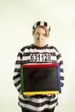 Kvinna i fängelselikformig med den svart tavlan Royaltyfri Fotografi
