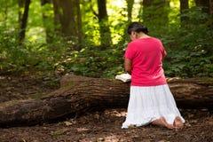 Kvinna i Forest Preserve med bibeln som knäfaller i bön royaltyfri bild