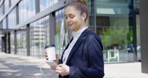 Kvinna i formellt med smartphonen och kaffe arkivfilmer