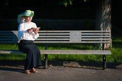 Kvinna i gammalmodig klänningläsebok Arkivbilder