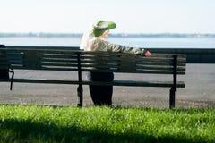 Kvinna i gammalmodigt klänningsammanträde på bänken Royaltyfri Fotografi