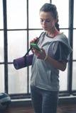 Kvinna i genomkörarekugghjul i vindidrottshall som kontrollerar mobiltelefonen Royaltyfri Foto