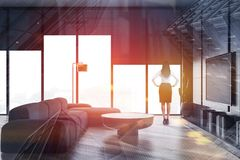 Kvinna i grå vardagsrum med TVuppsättningen arkivfoto