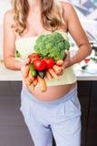 Kvinna i gravid sunda grönsaker för äta Royaltyfria Bilder
